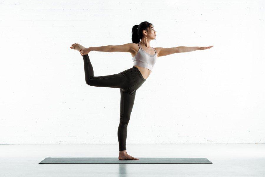 hugger mugger vs jade yoga mats - asian woman practicing yoga on black yoga mat