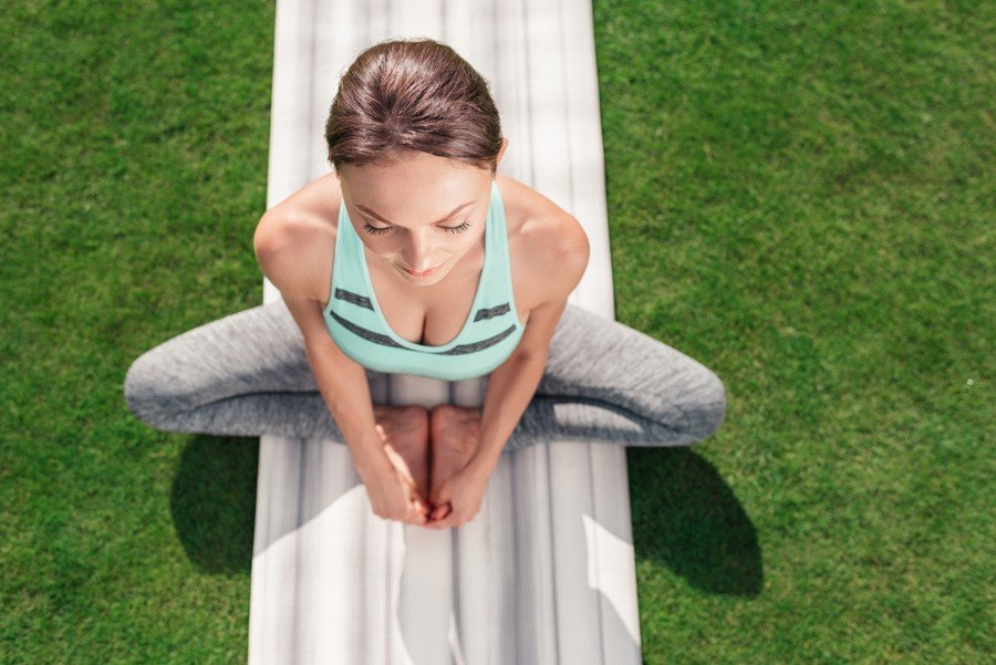 top down view of woman doing bound angle pose