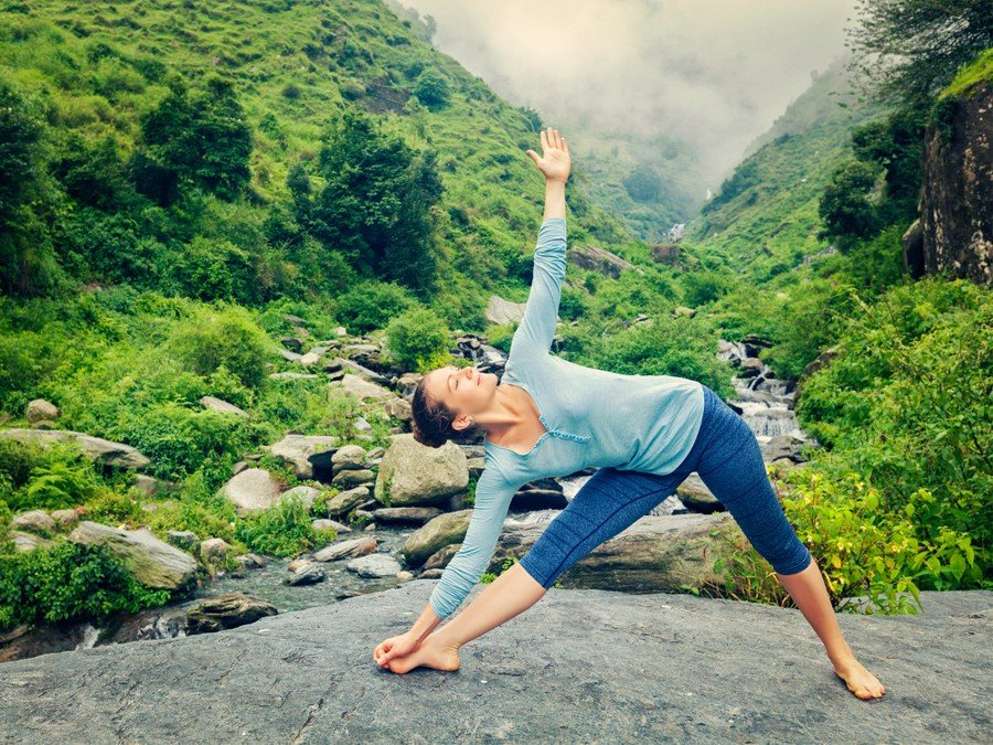 woman performing extended triangle pose on mountain