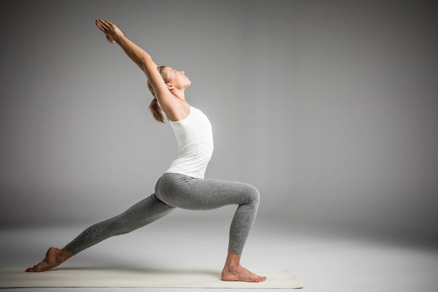 woman performing warrior one pose