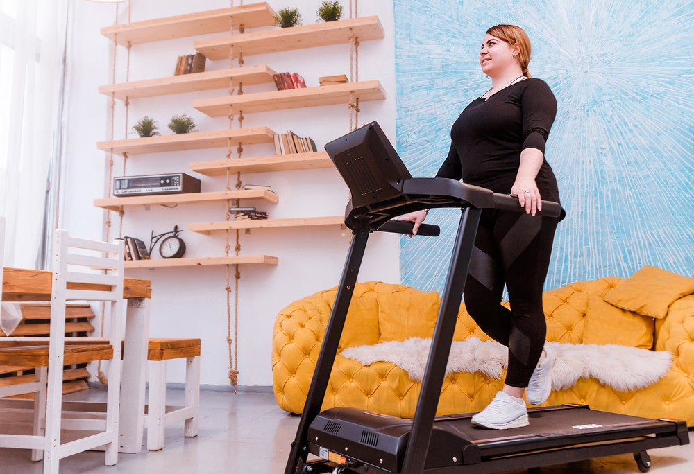 best folding treadmill - woman on treadmill in her house
