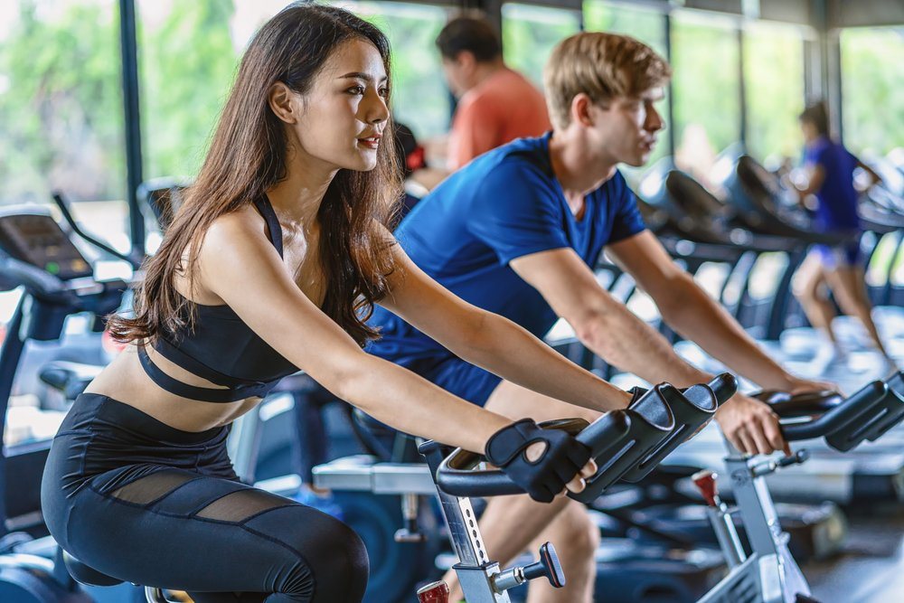 man and woman riding spin bikes