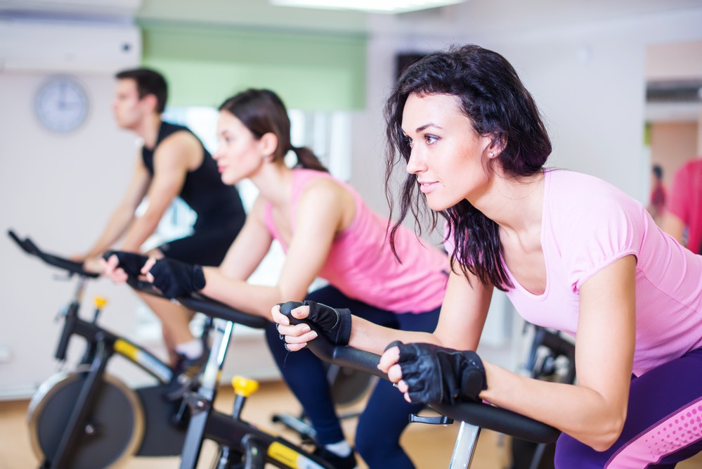 women and men on spin bikes