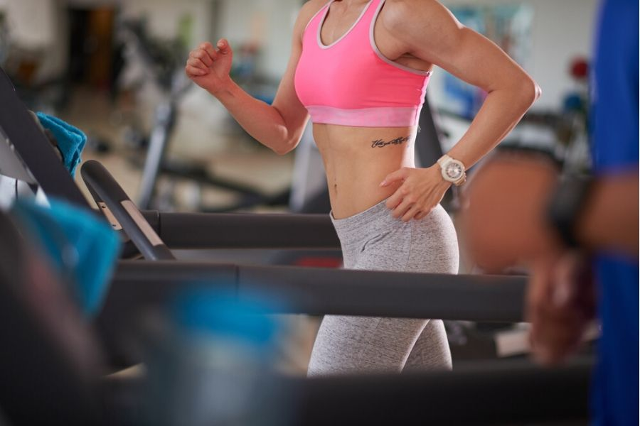 fit woman working out on manual treadmill