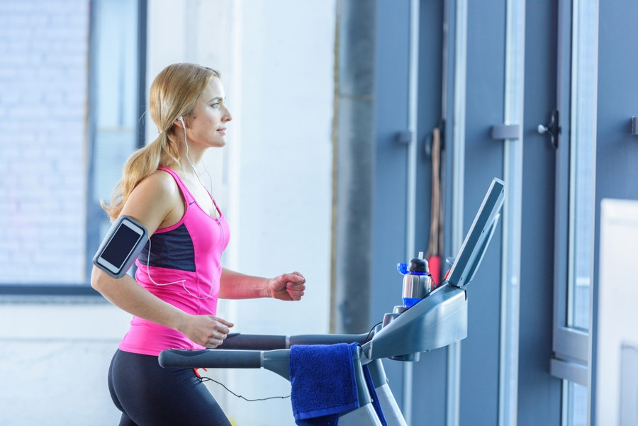 woman in pink shirt using the best compact treadmill