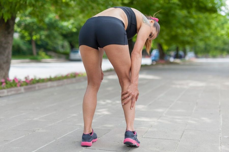 Female runner holding calves because they're in pain - best calf massagers