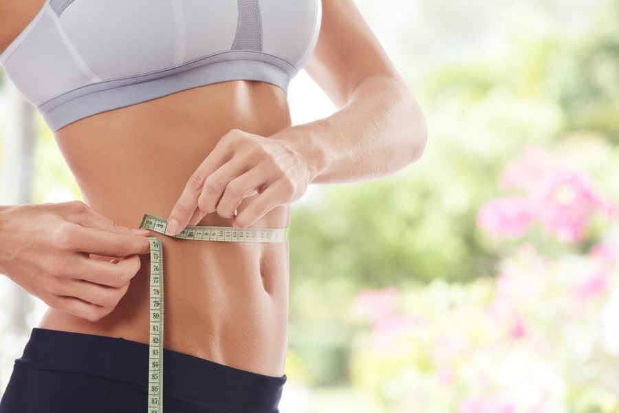 best waist trimmer - woman with slim waist and measuring tape