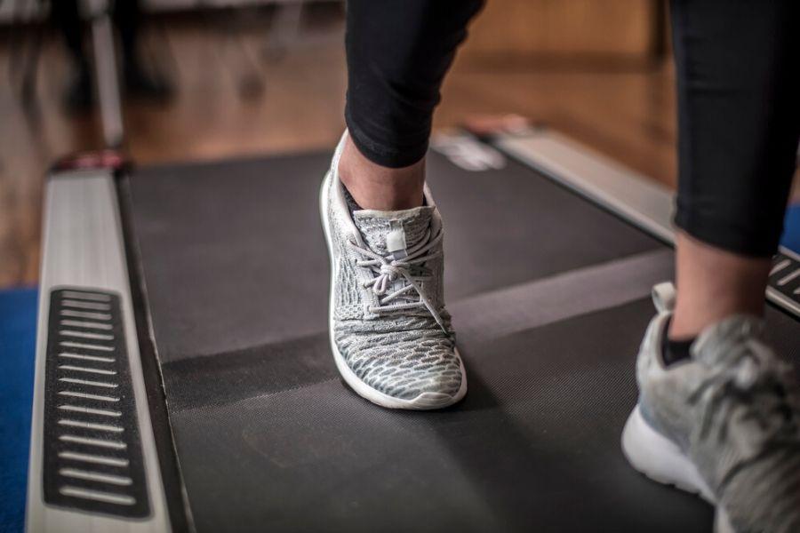 close up of womans feet walking on under desk treadmill