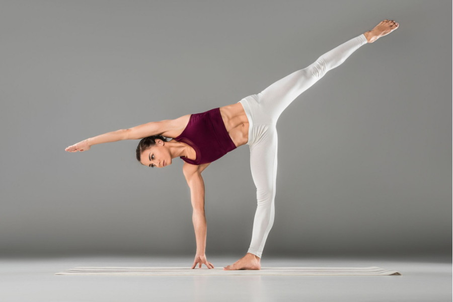 young woman doing yoga in white yoga pants