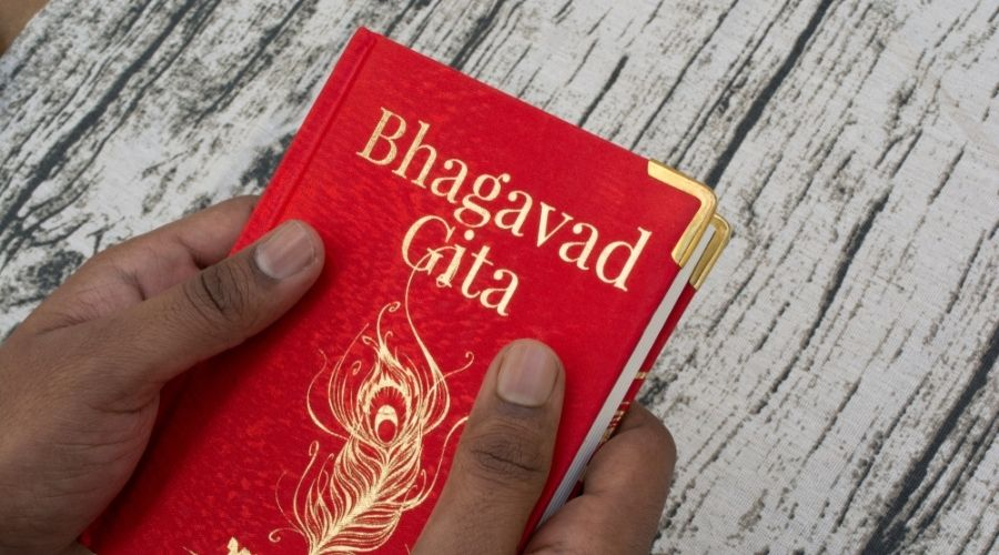 hands clutching the Bhagavad Gita