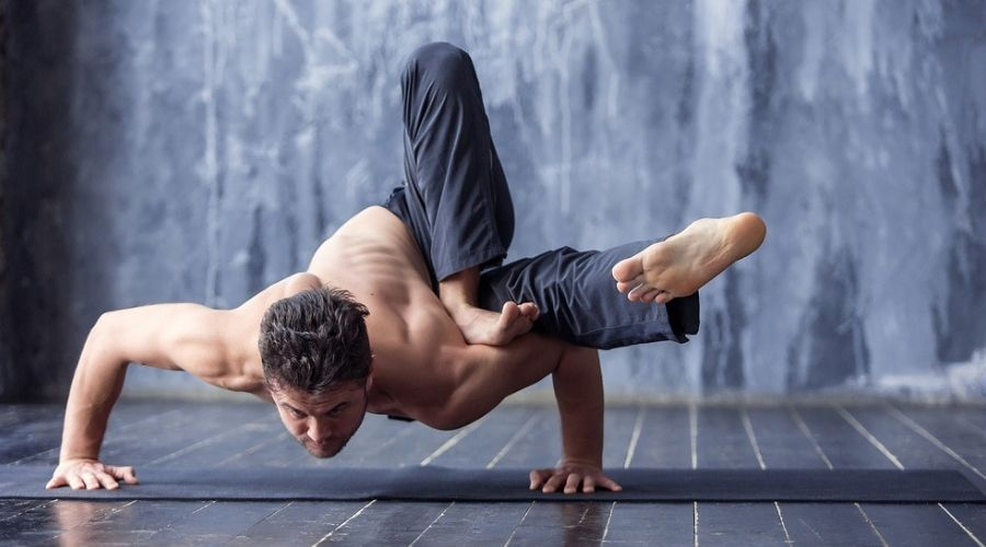 man doing very hard yoga pose in power yoga