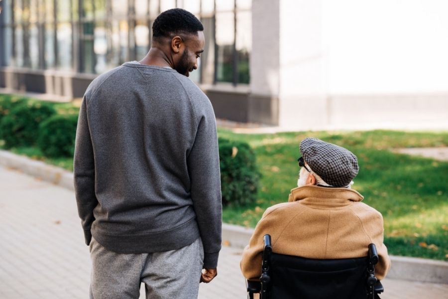 young african american man walking with older man in wheelchair