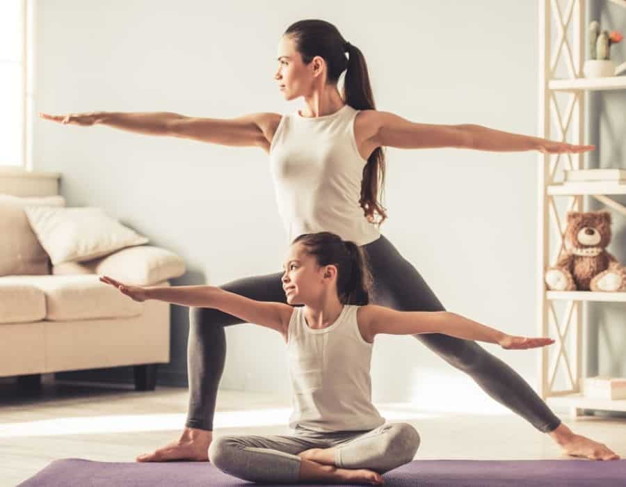 young mother teaching her daughter yoga
