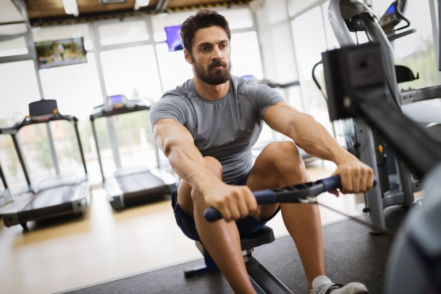 Man riding the sunny health and fitness rowing machine doing a review