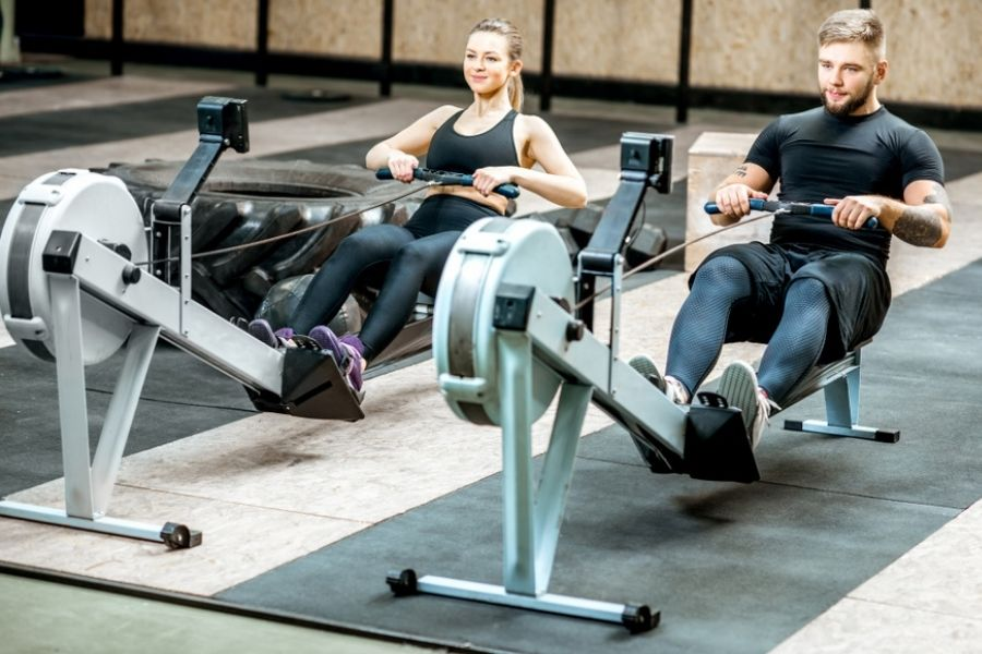 a couple using rowing machines in a gym