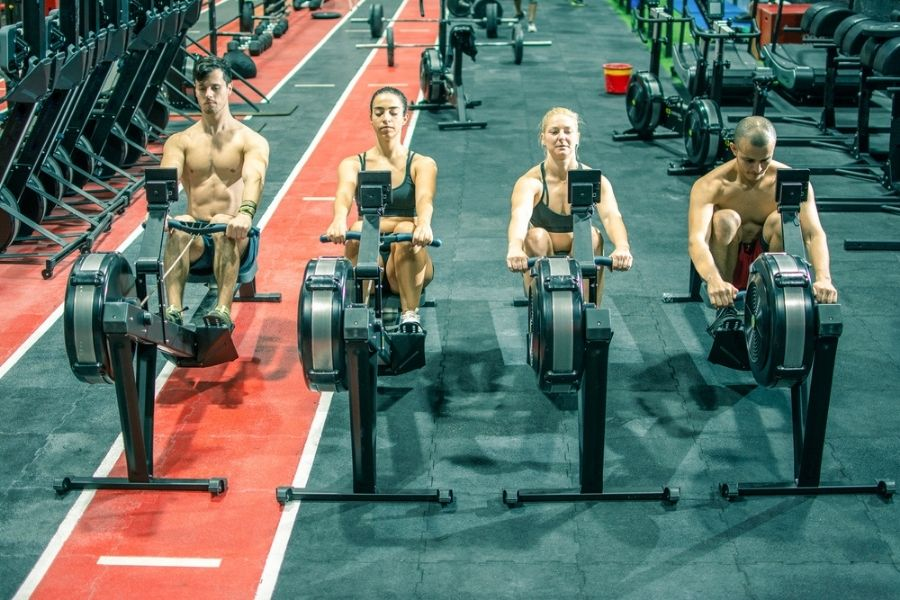 four people at crossfit competition on rowers