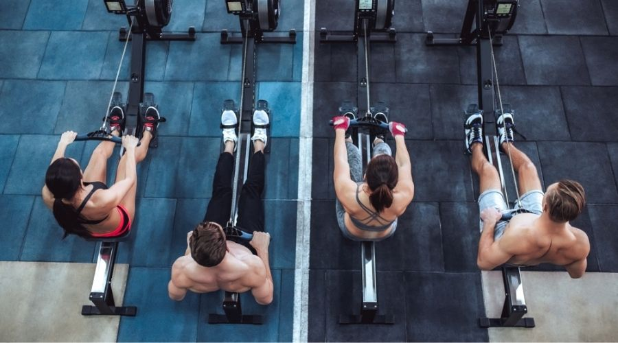 four people on rowing machines rowing next to each other