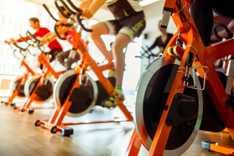 group spin class with orange spin bikes