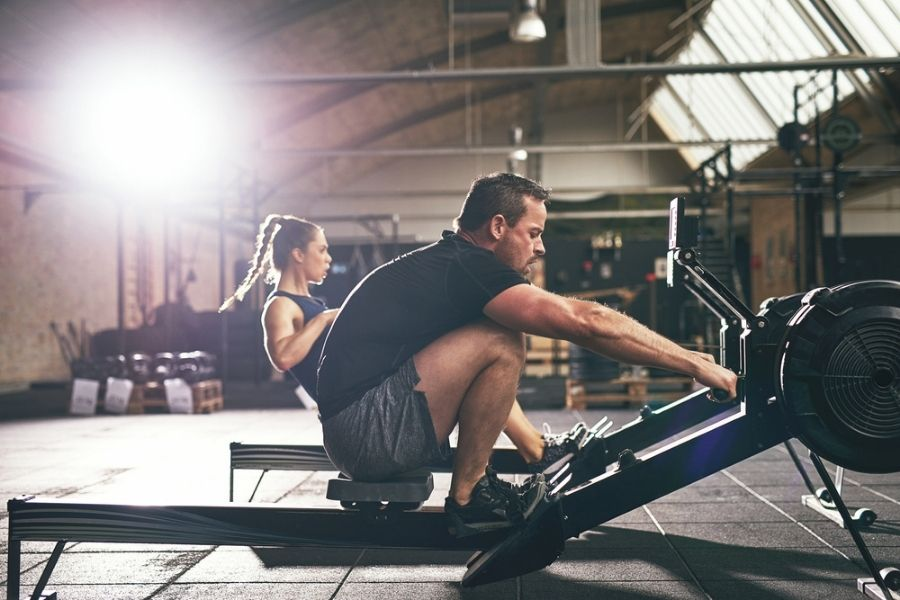 man and woman on rowing machine