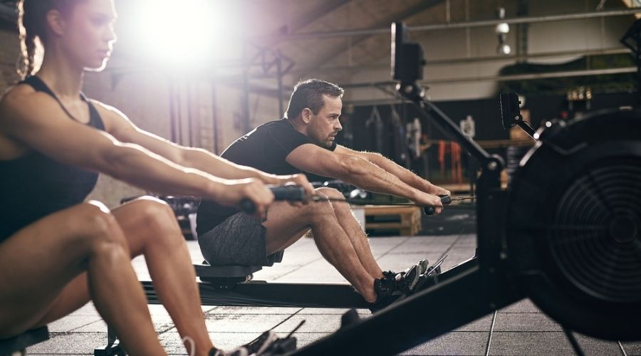 man and woman using rowing machines