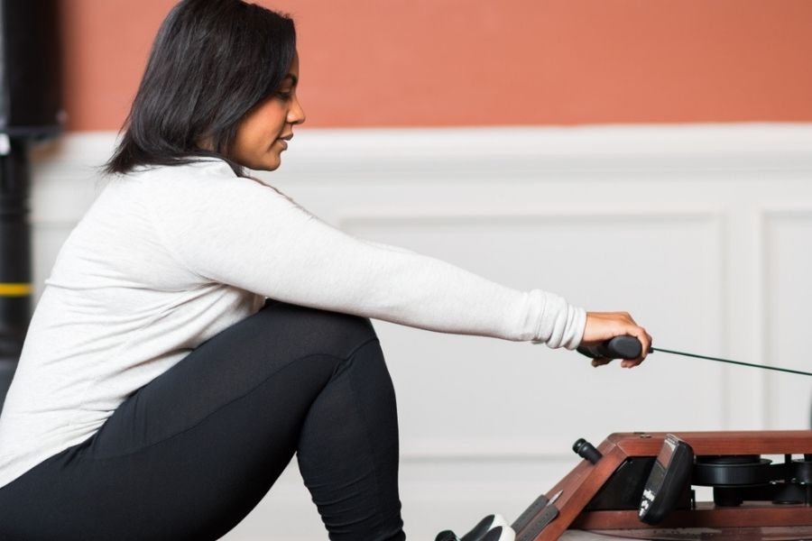 pretty woman using the water rower