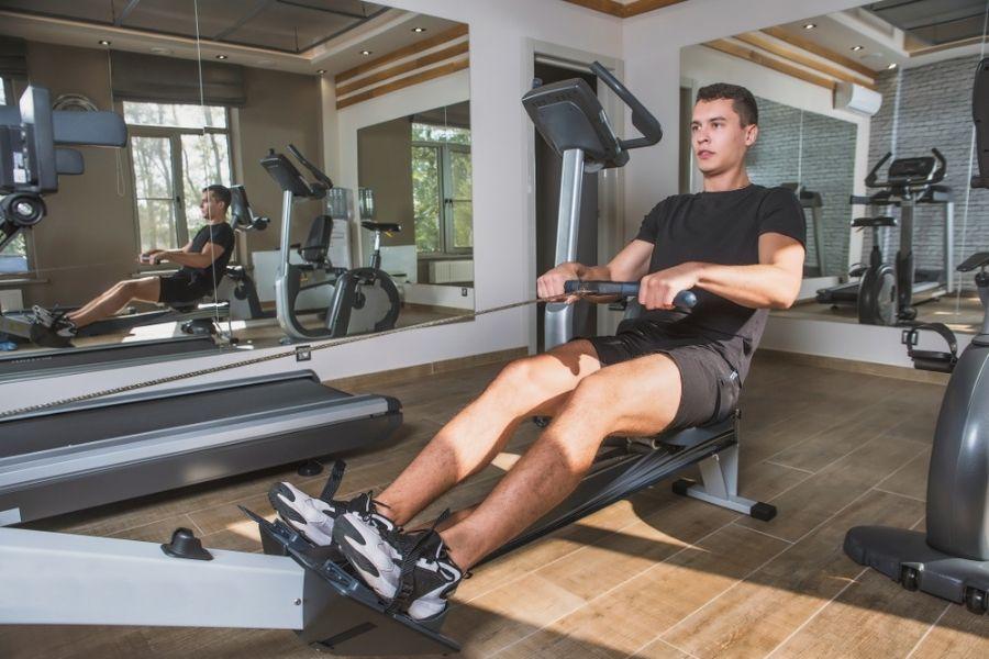rowing machine vs bike - man on rower with bike in background