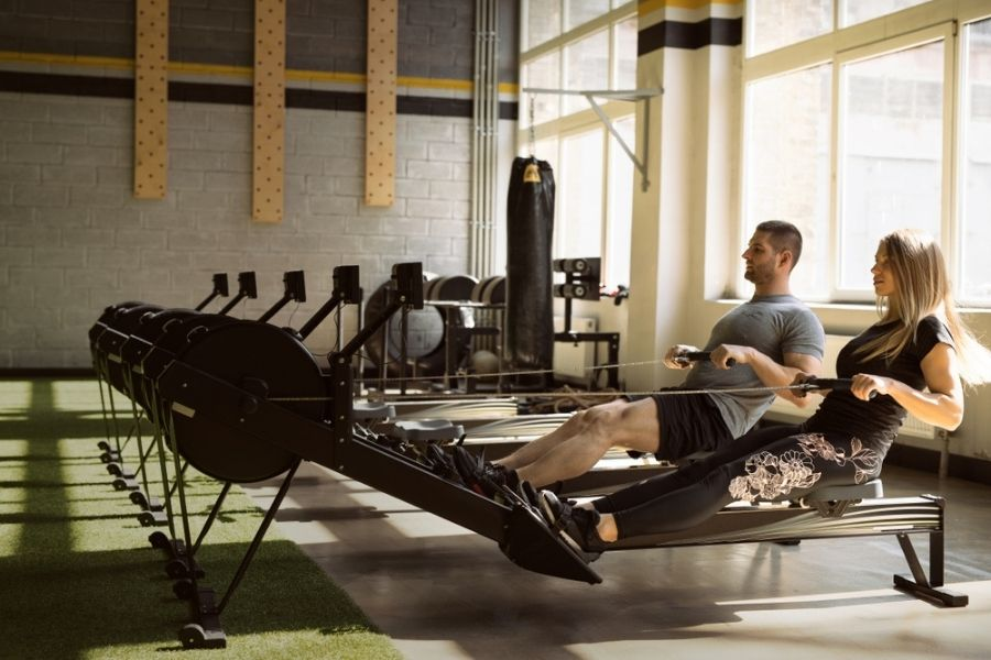 rowing machine workouts - fit couple working out on rowing machines