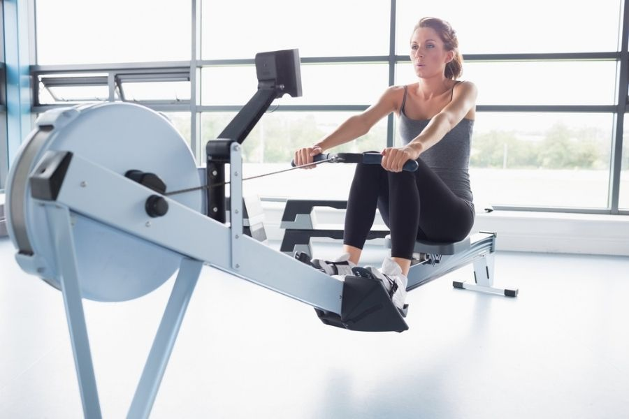 total gym vs rowing machine - woman on rower