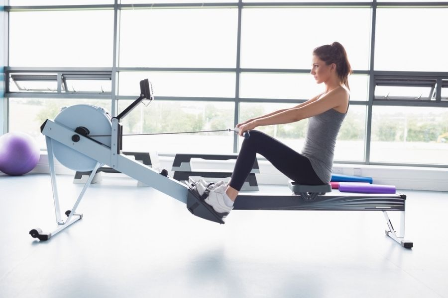 young pretty woman riding a rowing machine