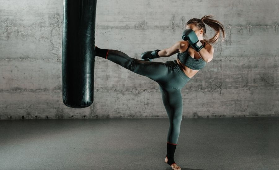 Best gym bags for boxing, mma, bjj and muay thai - pretty woman kicking martial arts bag