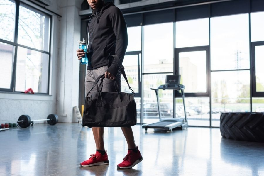 best gym bags for bodybuilders, powerlifting, and weightlifting - man in gym with bag