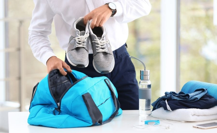 man packing shoes into gym bag