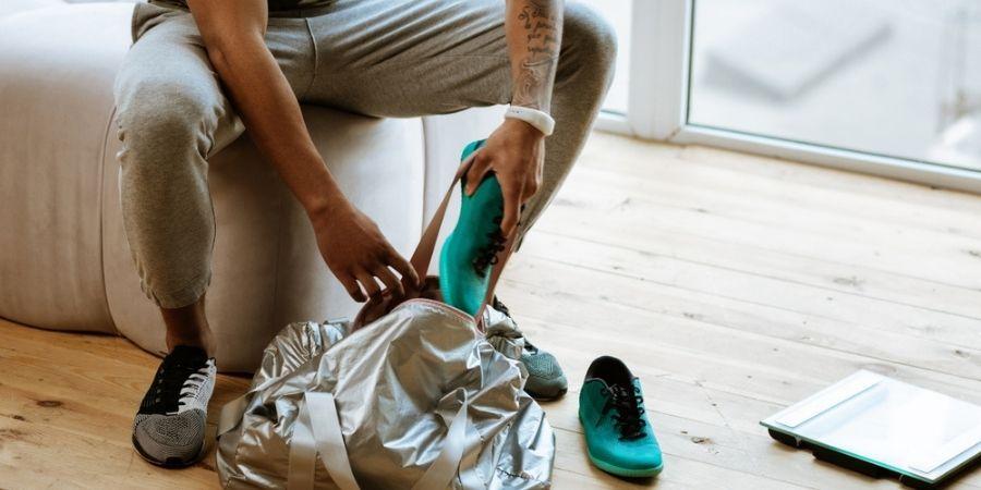 man putting items into workout bag