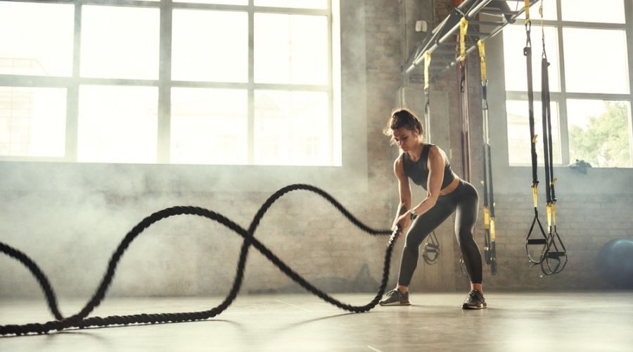 best crossfit gym bags - woman in the gym doing battle ropes