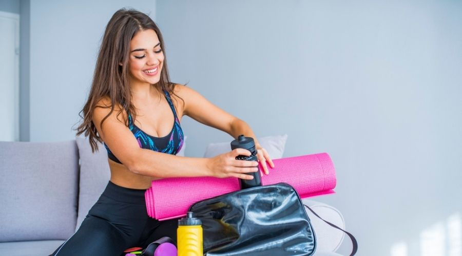 pretty woman packing items into a cute gym bag