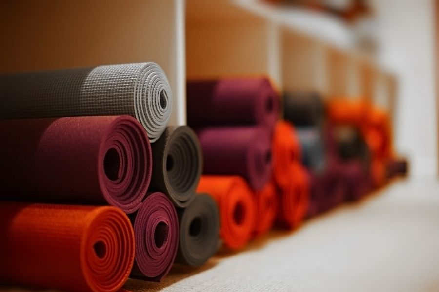 What are yoga mats made of - a variety of mats on a shelf