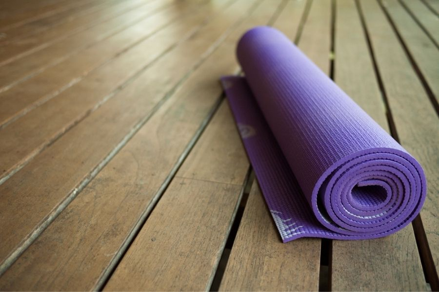 pvc yoga mat rolled up on a wood floor