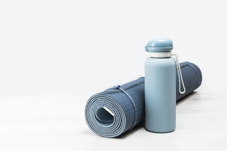 tpe yoga mat next to a water bottle on a white background
