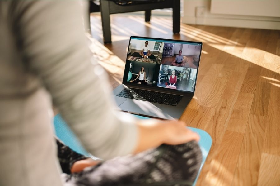 woman in front of laptop learning to become a yoga instructor