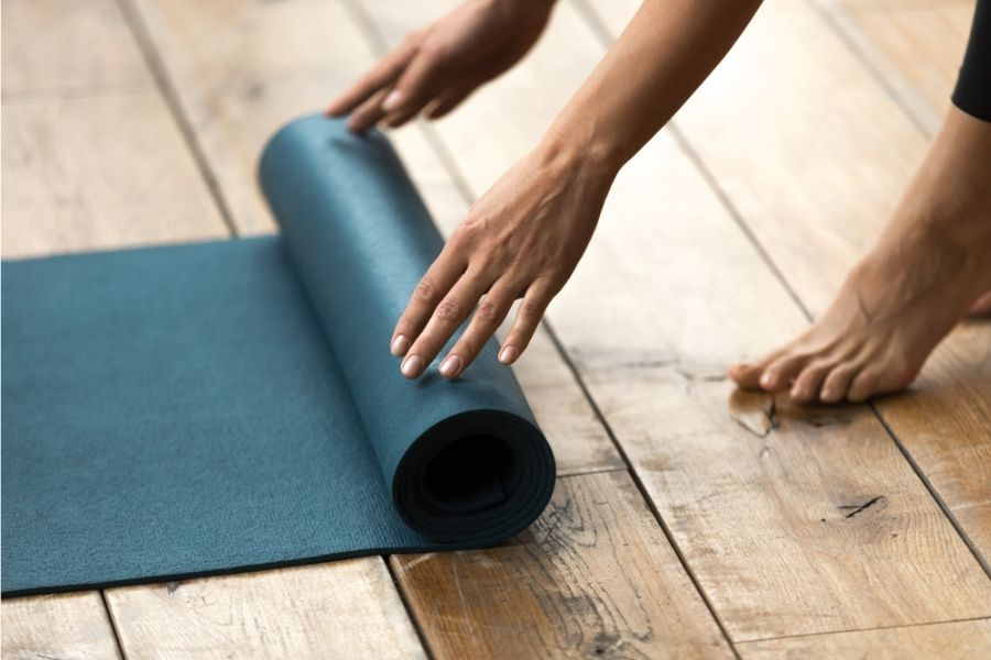 woman rolling up a natural rubber yoga mat