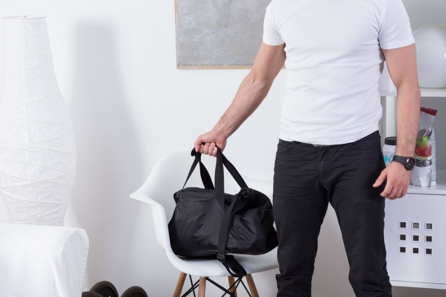 Man in white shirt and jeans picking up gym bag