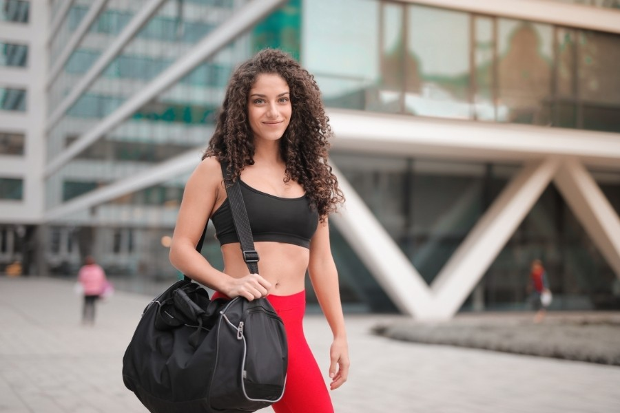 What to bring to the gym - young athletic woman holding a gym bag over her shoulder
