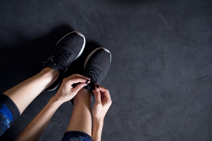 athlete lacing up workout sneakers