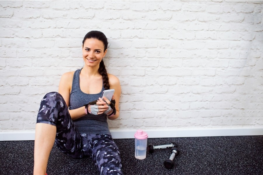 fit woman leaning up against a brick wall in workout clothing