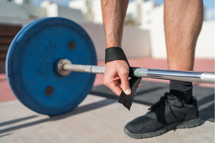 man wrapping lifting straps around an olympic barbell