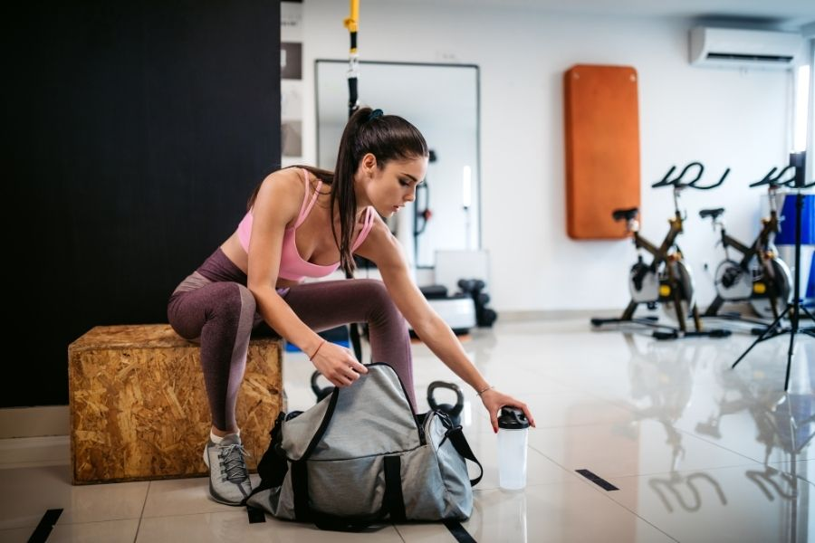young woman packing her gym bag